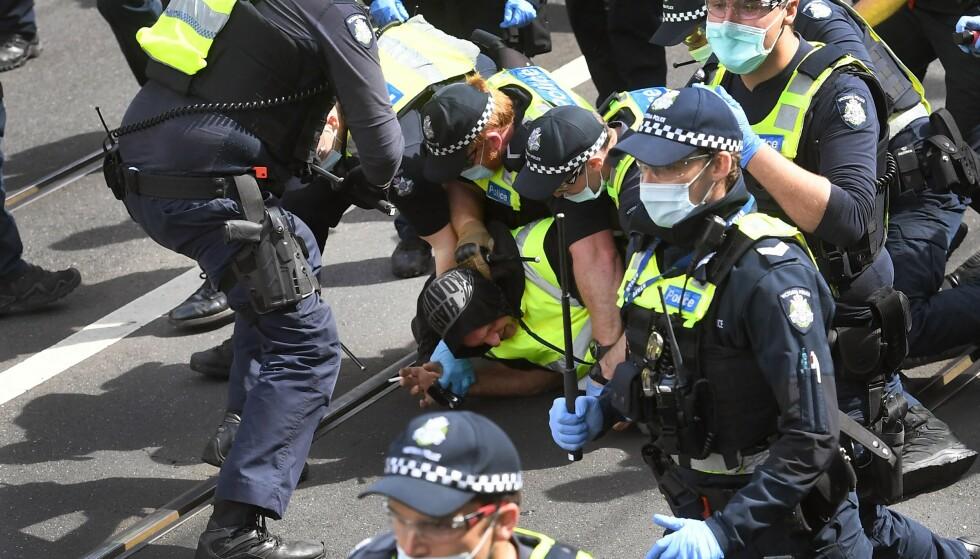 DEMONSTRASJON: En demonstrant blir lagt i bakken av politiet i Melbourne. Foto: NTB
