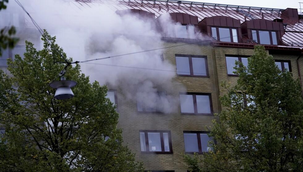 RØYK: Det velter store mengder røyk ut av bygården. Foto BJÖRN LARSSON ROSVALL / TT / NTB