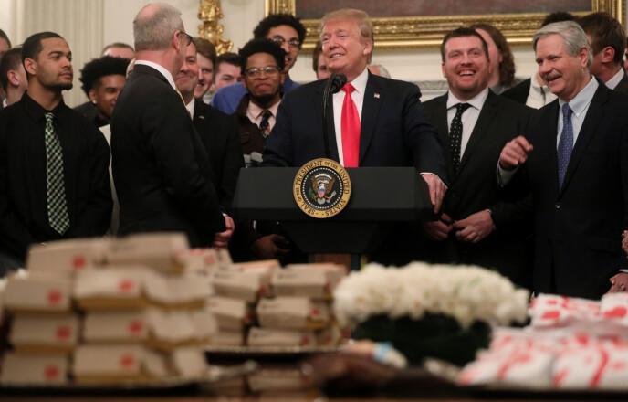 BON APPÉTIT #2: To måneder seinere gjentok Trump burger-stuntet, denne gangen med medlemmer av fotballaget North Dakota State Football. Foto: Jonathan Ernst / Reuters / NTB