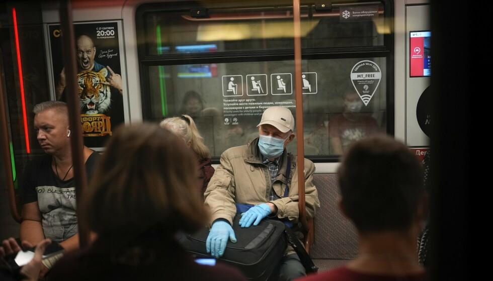 FÅ MUNNBIND: En eldre mann på metroen i Moskva beskytter seg så godt han kan mot covid-19. Men ellers er det få munnbind å se i den russiske hovedstaden selv om smittetrykket faktisk har økt den senere tid. Foto: AP / NTB